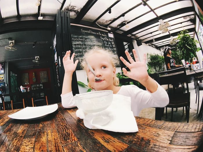 Child Childhood Cute Females Food And Drink Front View Girls Holding Indoors  Innocence Leisure Activity Lifestyles One Person Portrait Real People Restaurant Table Women