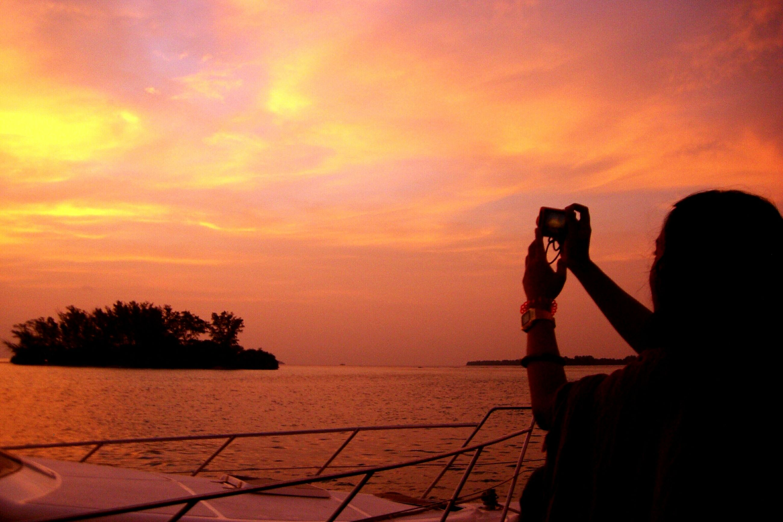 sunset, lifestyles, sky, leisure activity, water, sea, orange color, cloud - sky, silhouette, standing, horizon over water, beauty in nature, scenics, nature, holding, photography themes, photographing, sitting