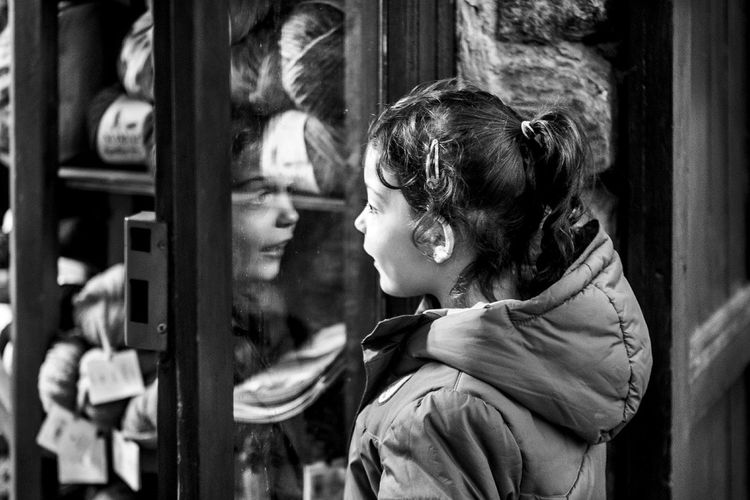 Side view of girl looking through window glass at store
