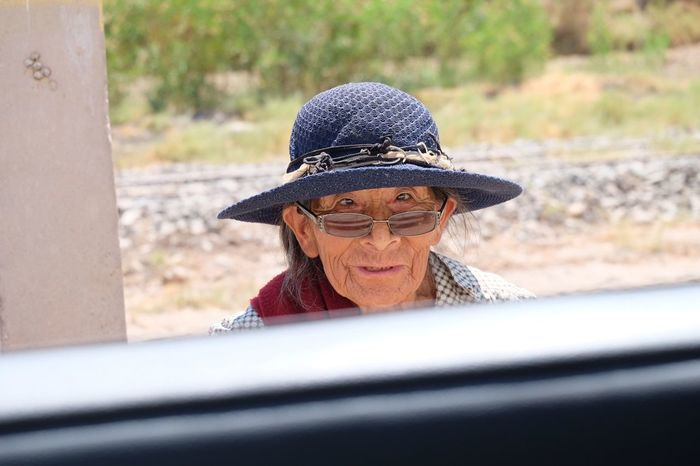 Elderly local woman with hat Female Charakter Blue Hat Car Window Local Woman Looking At Camera Senior Adult Sunglasses Press For Progress
