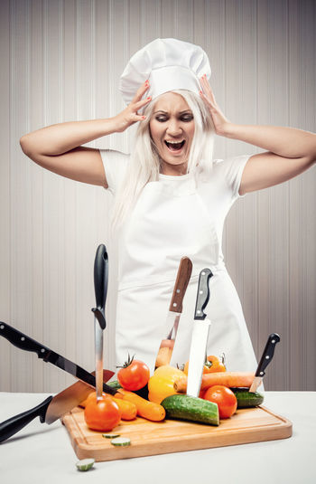 Woman cook Blonde Cook  Cooking Diet Knife Overworked Unhappy Vegetarian Food Caucasian Chef Cookery Depression Dieting Emotional Female Indoors  Nervous One Person Raw Vegetables Screaming Shouting Stressed Tired Vegetable Vegetables