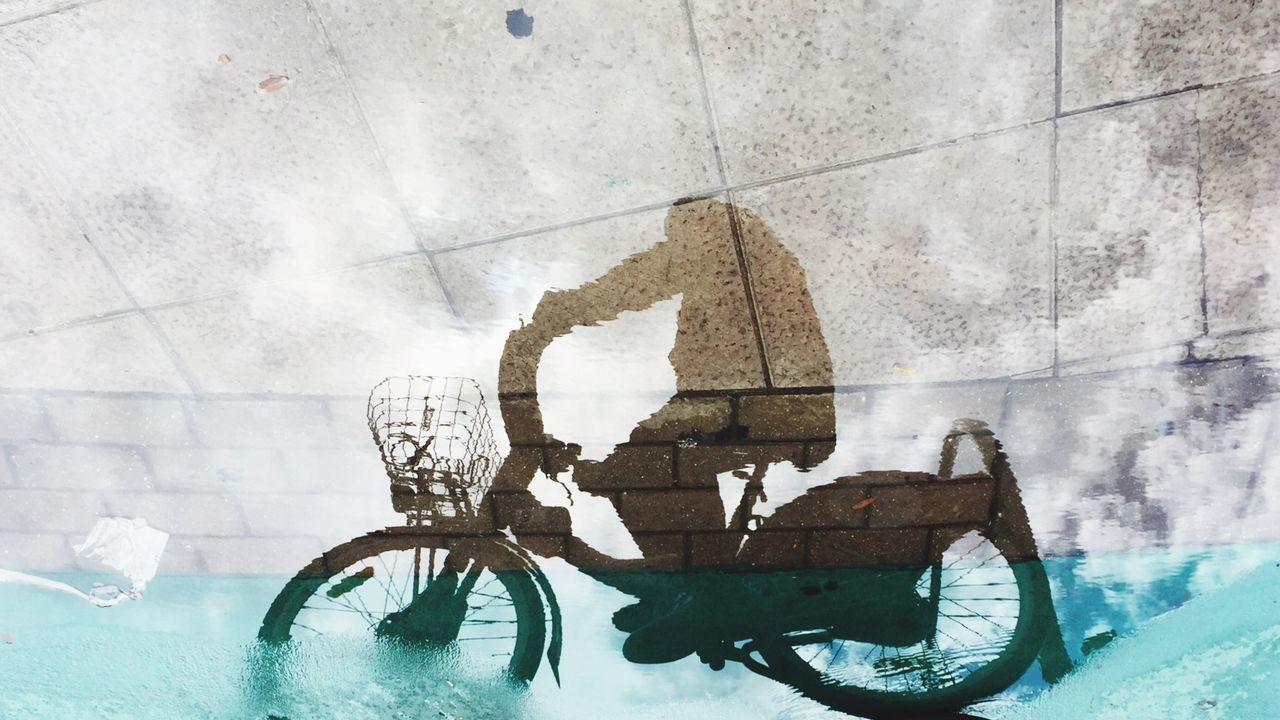 Reflection of person riding bicycle on water