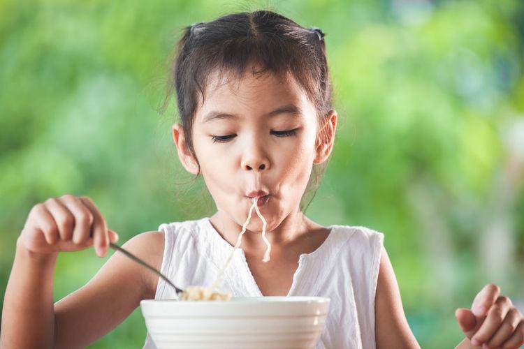 Cute girl eating noodles in public park