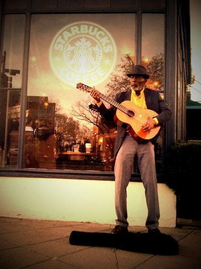 At the corner Starbucks in Dupont Circle, Washington, DC, a busker plays his tunes as the sun sets.
