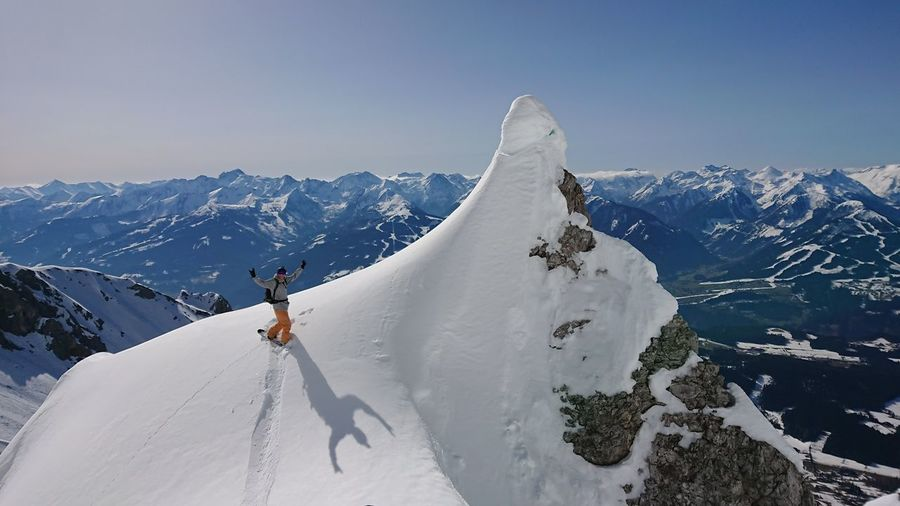 Man Snowboarding On Mountain Against Sky