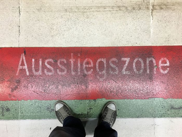 Low section of man standing by text on railroad station at frankfurt international airport
