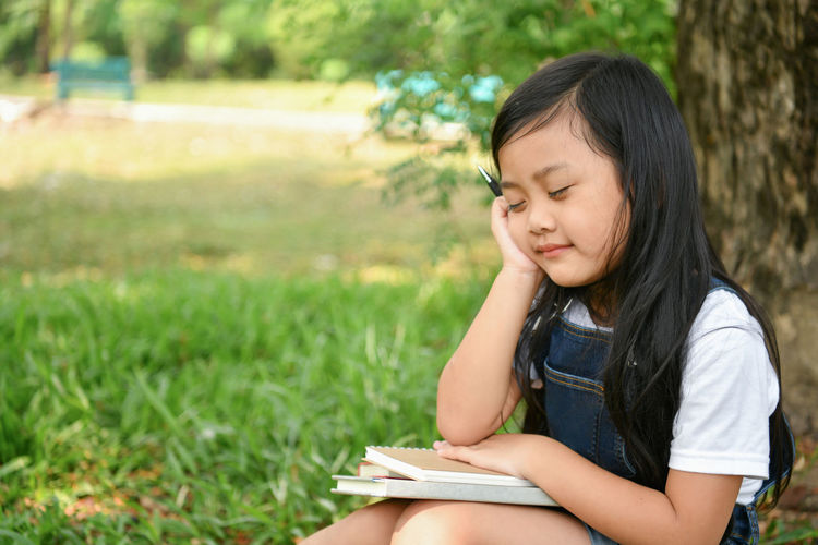 Girl With Eyes Closed Holding Books While Sitting On Grassy Field At Park