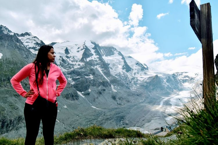 Young woman standing on snowcapped mountain against sky