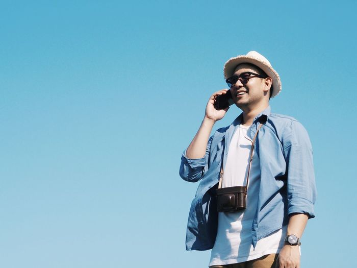 Low angle view of smiling man using phone against clear blue sky