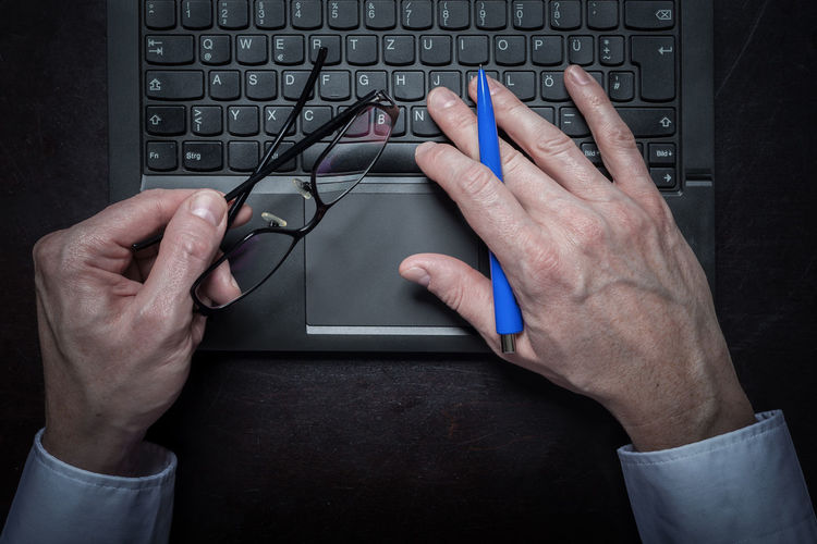 Cropped hands of businessman using laptop at desk