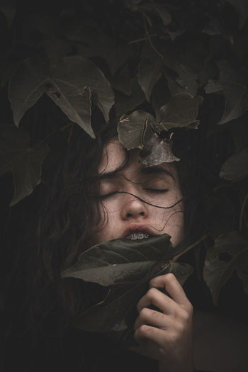 Close-up of woman with eyes closed amidst plants