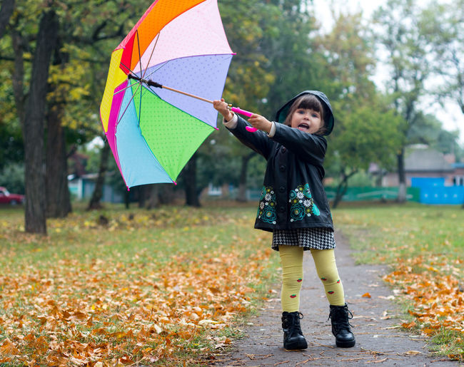 Portrait of girl holding colorful umbrella while standing on road during autumn