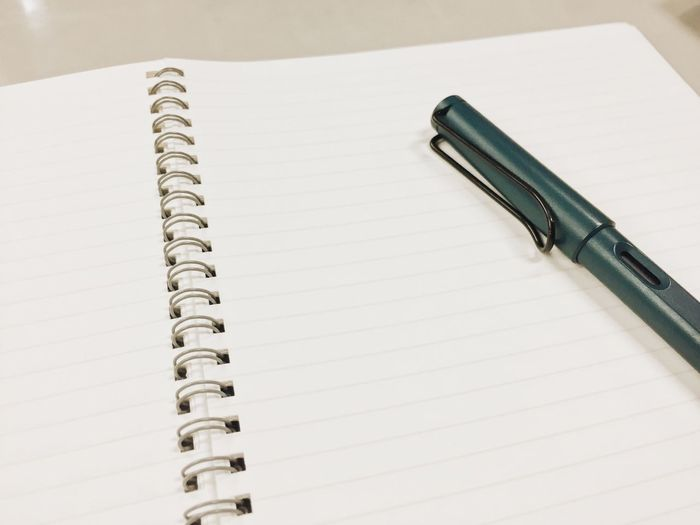 High angle view of pen on spiral notebook