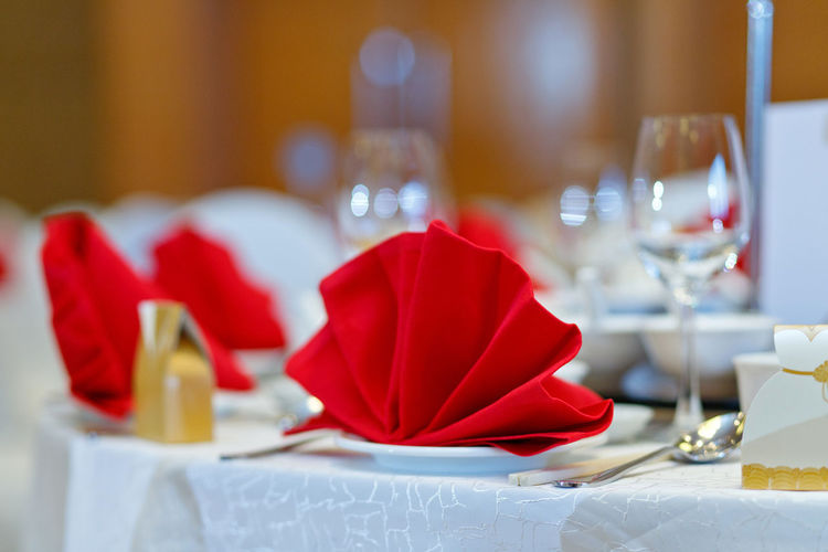Restaurant table setting Red Table Glass Setting Celebration Place Setting Wineglass Household Equipment Indoors  Drinking Glass Restaurant Elégance Napkin No People Furniture Food And Drink Decoration Dining Table Focus On Foreground Plate Table Knife Luxury