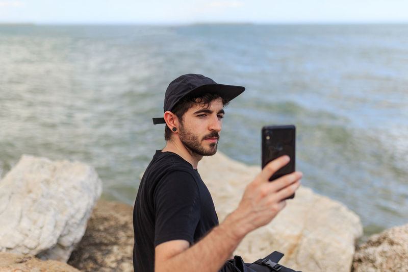 Young man using mobile phone in sea