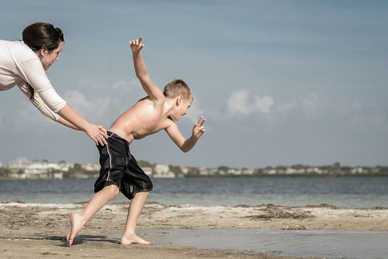 Side view of mother and son playing on beach