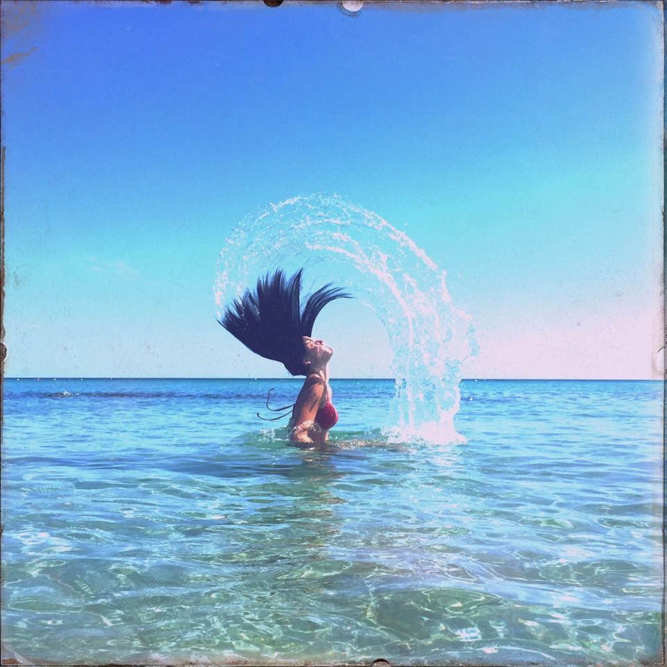 water, leisure activity, sea, lifestyles, waterfront, clear sky, enjoyment, full length, blue, motion, fun, swimming pool, splashing, vacations, young adult, copy space, horizon over water, swimming