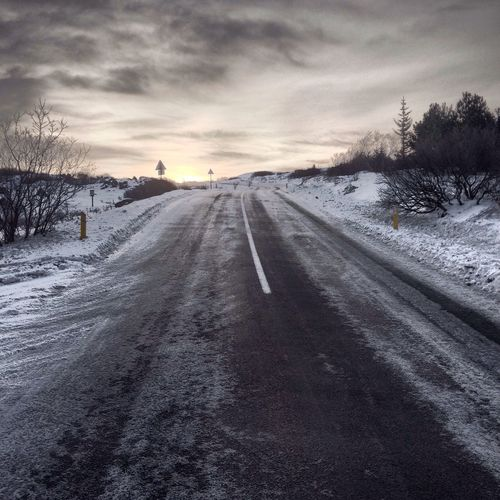 Snow covered road amidst field against sky during winter