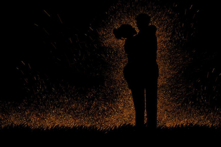 Silhouette people standing on field at night