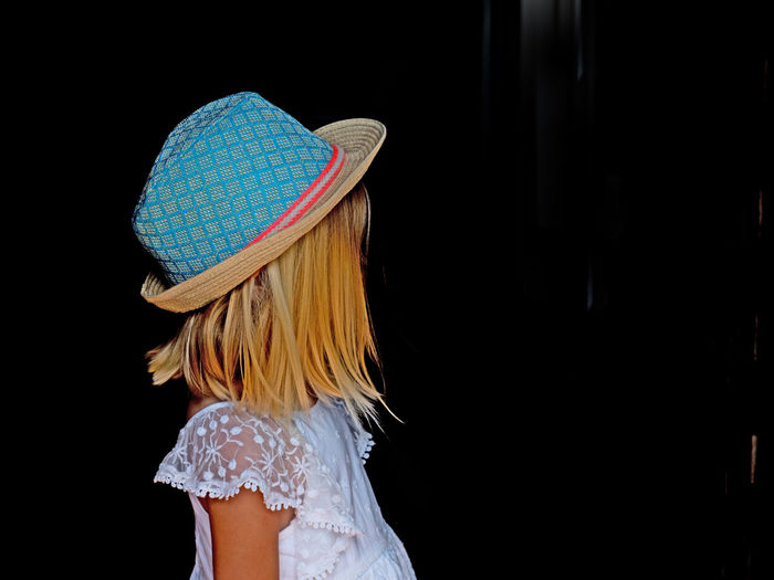 Blue Hat Black Background Blond Hair Child Childhood Clothing Females Girls Hair Hairstyle Hat Human Hair Indoors  Innocence Leisure Activity Lifestyles Long Hair One Person Real People Standing Studio Shot Women