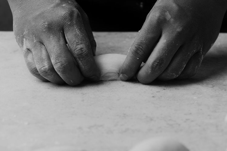 Cropped hands of person kneading dough