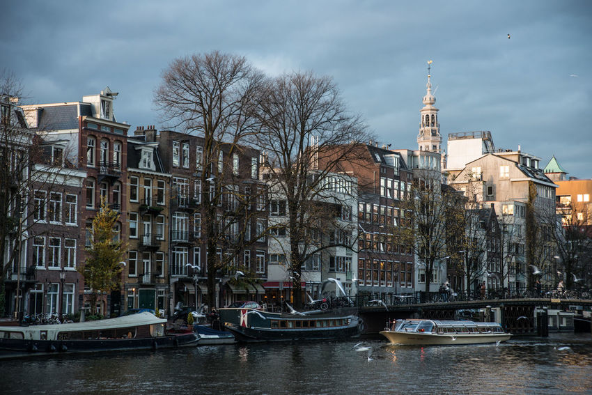 Amsterdam Eveing Historical Building Architecture Bare Tree Building Exterior Built Structure Canal City Day Mode Of Transport Nature Nautical Vessel No People Old City Outdoors Sky Transportation Tree Twighlight Water Waterfront