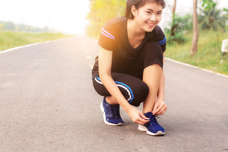 Smiling Young Woman Tying Shoelace While Crouching On Road