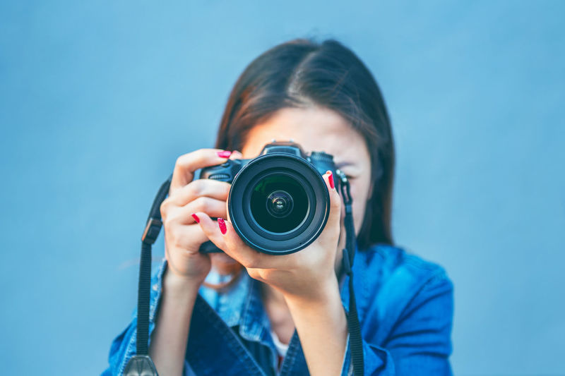 Woman photographing through camera against blue background
