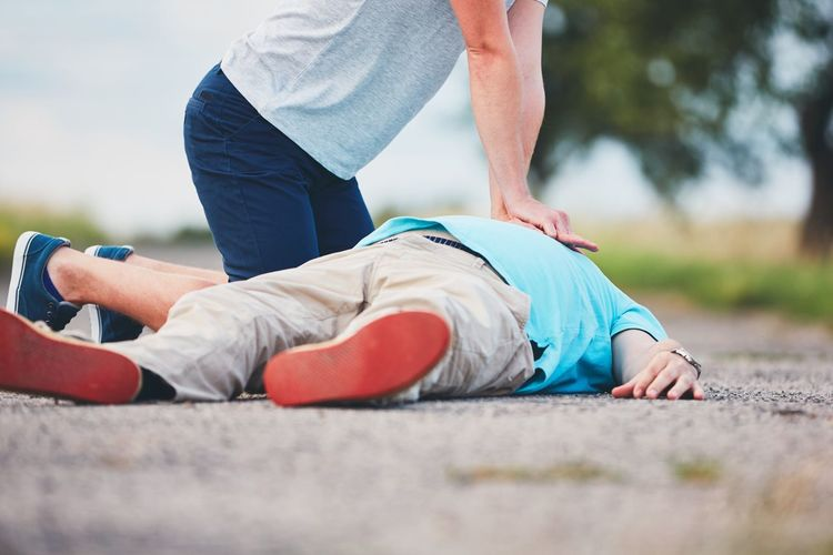 Low section of man resuscitating friend lying on road