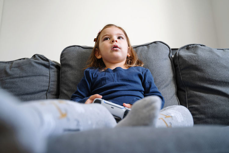 Girl looking away while sitting on sofa at home