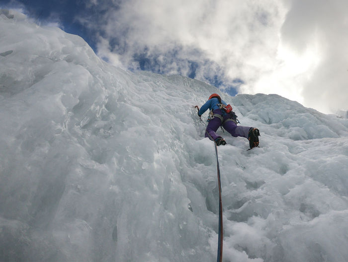 Alpinist woman with ice tools axe in orange helmet climbing a large wall of ice. Cold Temperature Winter Snow Leisure Activity Real People Mountain Sport Adventure Cloud - Sky One Person Lifestyles Sky Beauty In Nature Day Holiday Scenics - Nature White Color Warm Clothing Outdoors Snowcapped Mountain Ice Climbing Woman Climber Slovenia  Ice Fall
