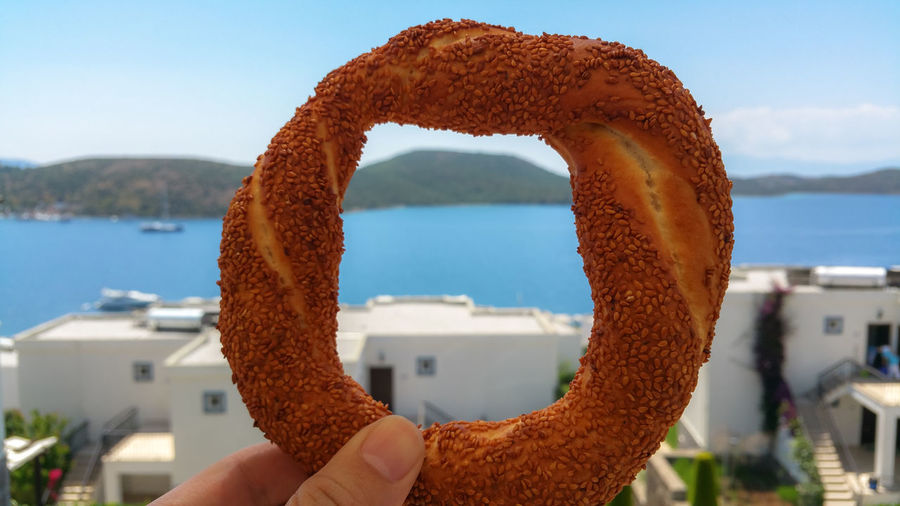 Close-up of person holding pretzel against sea