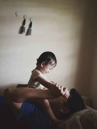 Father playing with daughter while lying on bed at home