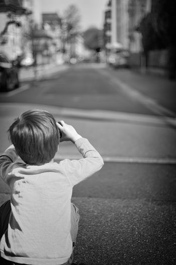 Rear view of boy with umbrella on road in city