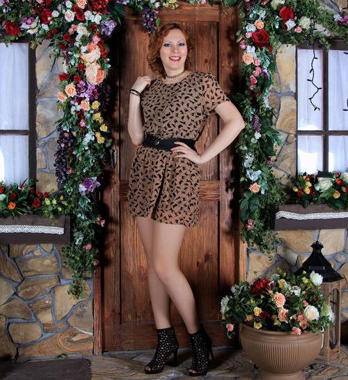 Incredible long legged redhead girl in fishnet stockings and minidress posing at wall