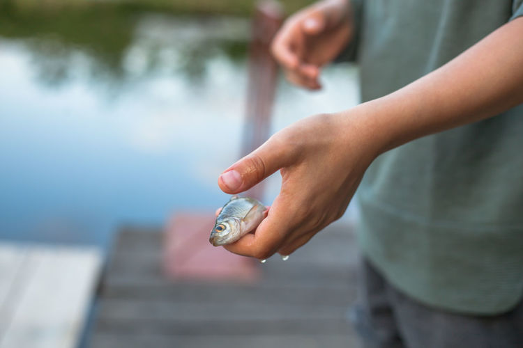 Midsection of boy holding fish on pier over lake