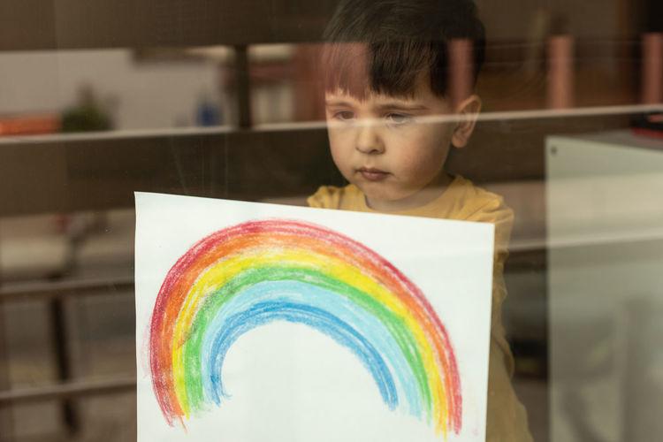 Portrait of cute boy against multi colored background