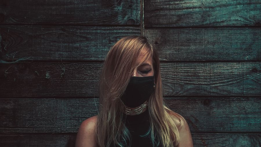 Young Woman Wearing Mask Against Wooden Wall
