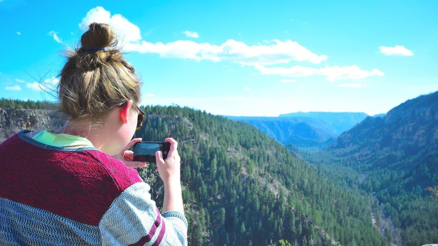 Rear view of woman photographing mountains against sky at oak creek canyon