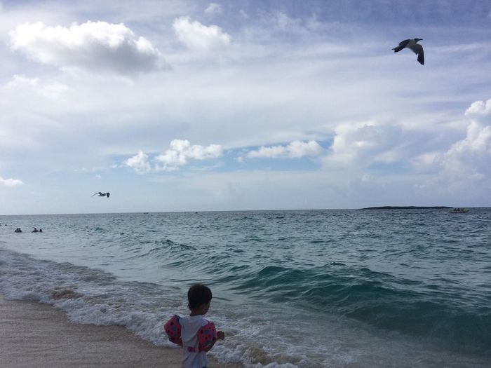 Rear view of boy with water wings standing on shore at beach