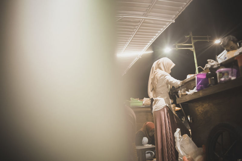 Woman working at market in night