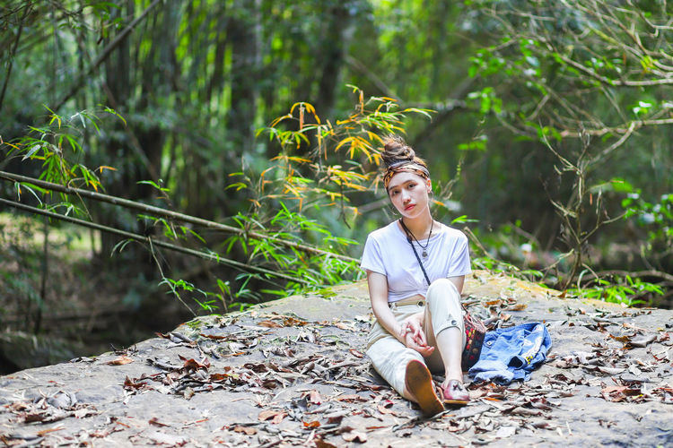 Portrait of serious young woman sitting on rock against trees in forest