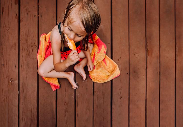 High angle view of girl eating popsicle while sitting on wood