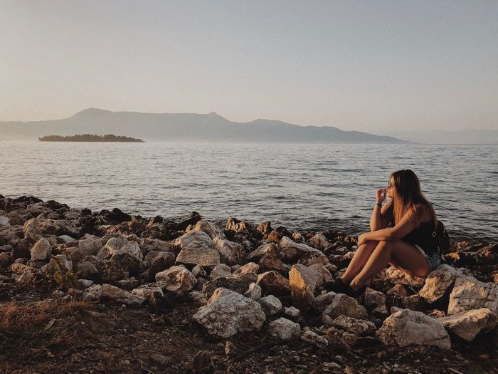 Sea Water Beach Land One Person Leisure Activity Lifestyles Women Beauty In Nature Nature Sky Real People Sitting Holiday Rock Vacations Scenics - Nature Trip Outdoors