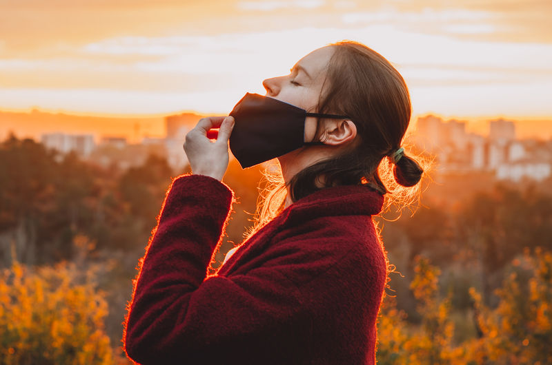 Portrait of a young woman taking a gulp of air from under mask during sunset