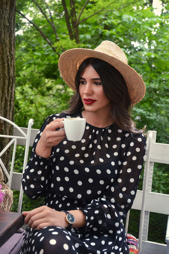 Young woman drinking coffee while sitting on tree