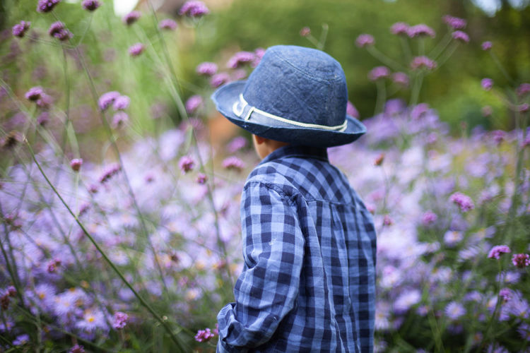 Rear view of person wearing hat standing against plants