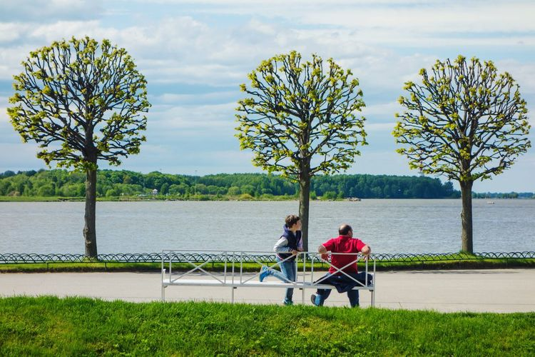 People sitting on bench by river