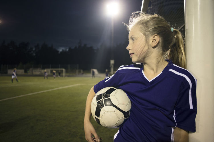 Young woman with ball in background at night
