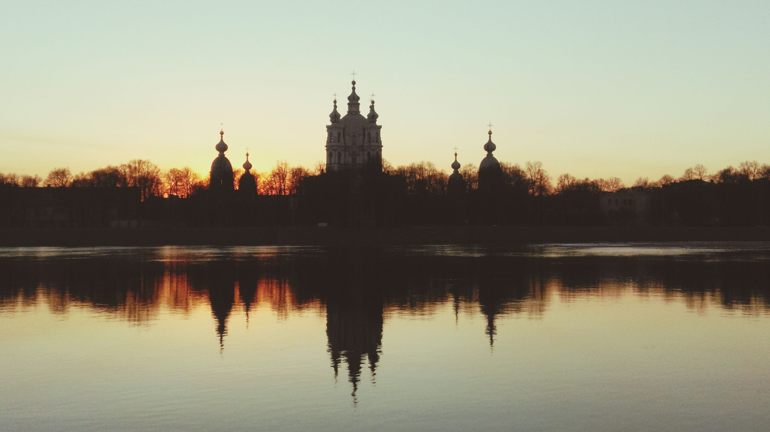 architecture, building exterior, built structure, sunset, reflection, water, waterfront, clear sky, lake, river, silhouette, copy space, tree, sky, tower, religion, spirituality, place of worship, orange color, travel destinations